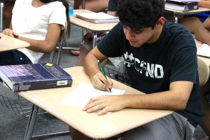 Junior Jose Castillo takes notes with traditional pen and paper in Kevin Casey's AP US History on Thursday.