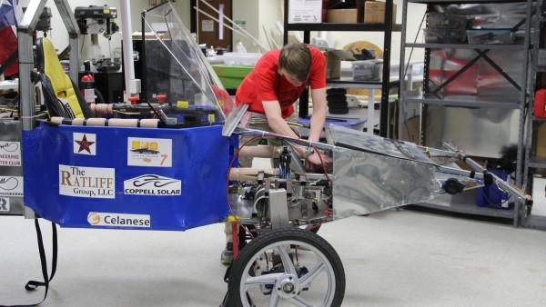 The Coppell High School solar car, which was raced over the summer, stays in STEM coordinator Mike Yakubovsky room, while Stephen Bavousett works on improving it for team's next race.