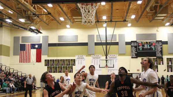 Late in the third quarter, sophomore guard Sam Marshall and senior forward Collin Wallace (30) both try to gain position to go up for a rebound over Plano West defenders. After jumping to a 15 point lead in the third quarter, West won 69-60, moving on the the third round of the playoffs. Photo by Nicole Messer.