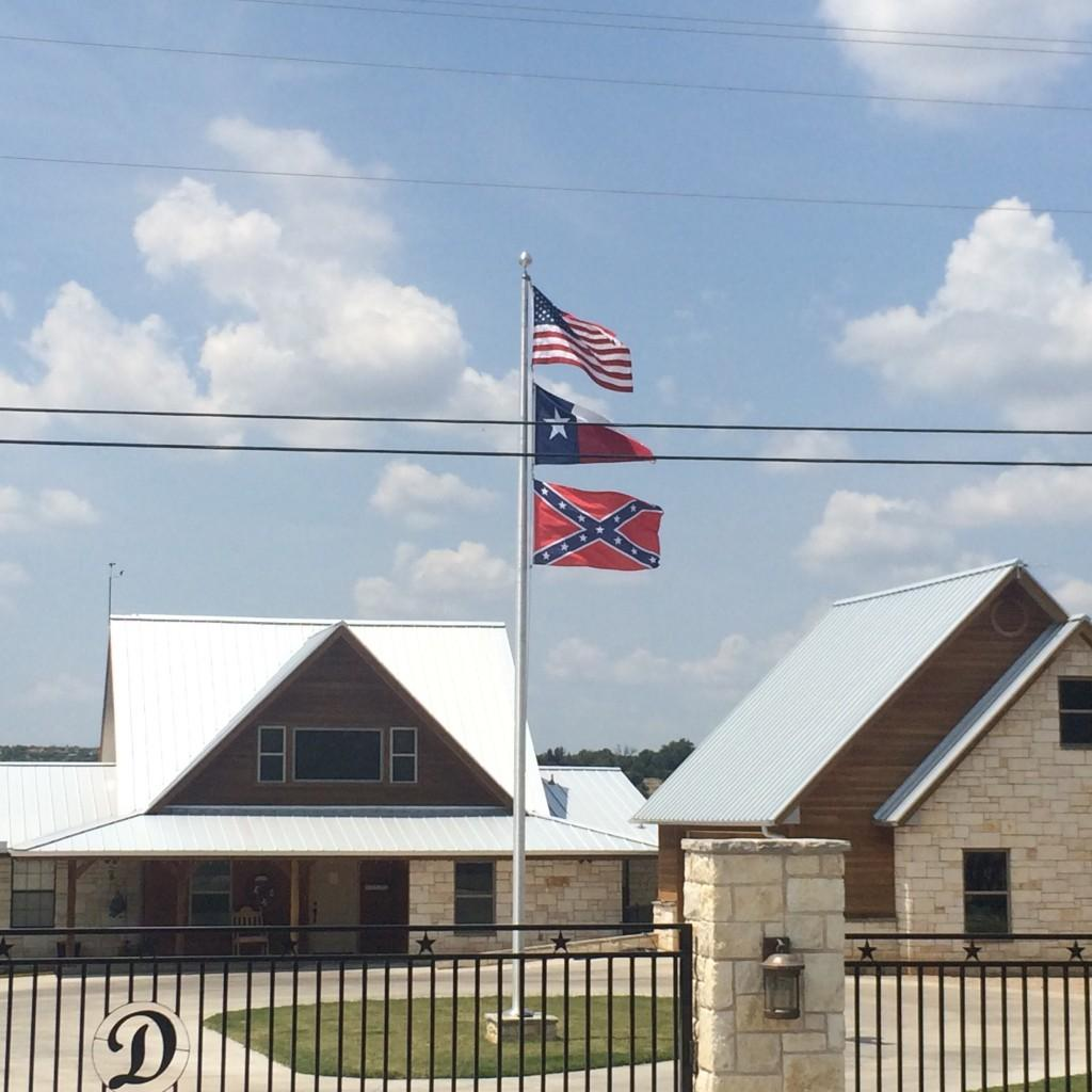 The confederate battle flag flying alongside the American, and Texan flag over a general store in Graford, Texas. Photo Courtesy Nicolas Henderson.