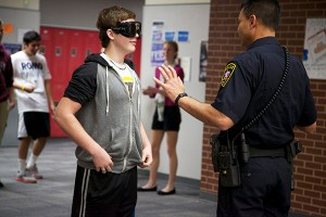 Dec. 19, On-campus school officer Ricky Jimenez explains to junior Kyle Ash how wearing the fatal vision googles impairs your vision and how standardized field sobriety test works in science teacher Susan Shepperd's forensic science class. Photo by Rowan Khazendar.