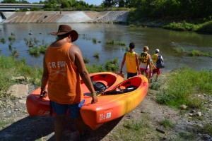 Trinity River Kayak Co. employees A.J. Date and Greg Ludden lead a family down to the river, bringing with them the kayaks the customers will be using. The family spent around three hours kayaking down the Trinity River on Sunday morning. Photo by Sandy Iyer.