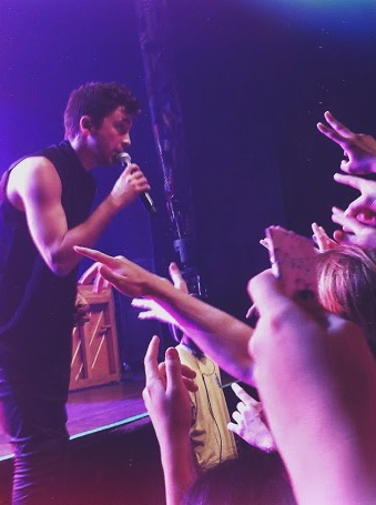 """Tyler Joseph gets up close and personal with the crowd as he sings """"Migraine""""."""