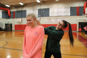 Seniors Holly Swaldi (left) and Annie Friedman (right) practice a self defense technique at the Coppell Middle School East gym.