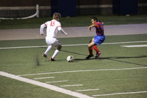 Senior forward Justin Todd maneuvers the ball into position for a cross as a Duncanville defender impedes his path to the goal in Coppell's UIL Regional Quarterfinal match against the Panthers on Apr. 8. The Cowboys will face Flower Mound Marcus in the Region I final match on Saturday afternoon at 2 p.m.  Photo by Shannon Wilkinson.