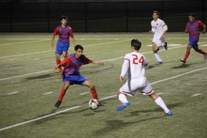 Coppell junior forward Colten Clark manuevers the ball around a Duncanville player in Tuesday's regional quarterfinal match at Birdville ISD Fine Arts/Athletic Complex. Coppell defeated Duncanville 2-0. Photo by Shannon Wilkinson.
