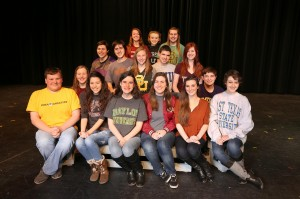Senior theater students pose with their college t-shirts on the Coppell High School stage.