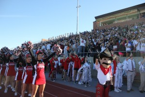 Coppell High School students raise their guns while singing their school song Oct. 17 at the homecoming pep rally in Buddy Echols Stadium. Photo by Nicole Messer.