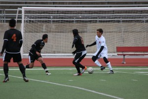 Senior Austin Michaelis dribbles between two WT White defenders Saturday Jan. 10. Coppell routed White 11-1.
