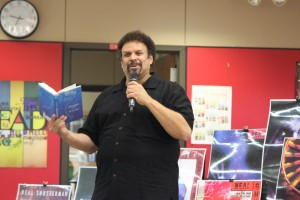 """Author Neal Shusterman reads a paragraph of his new release """"Challenge Deep"""" to describe his creative process to students. Photo by Kelly Monaghan."""