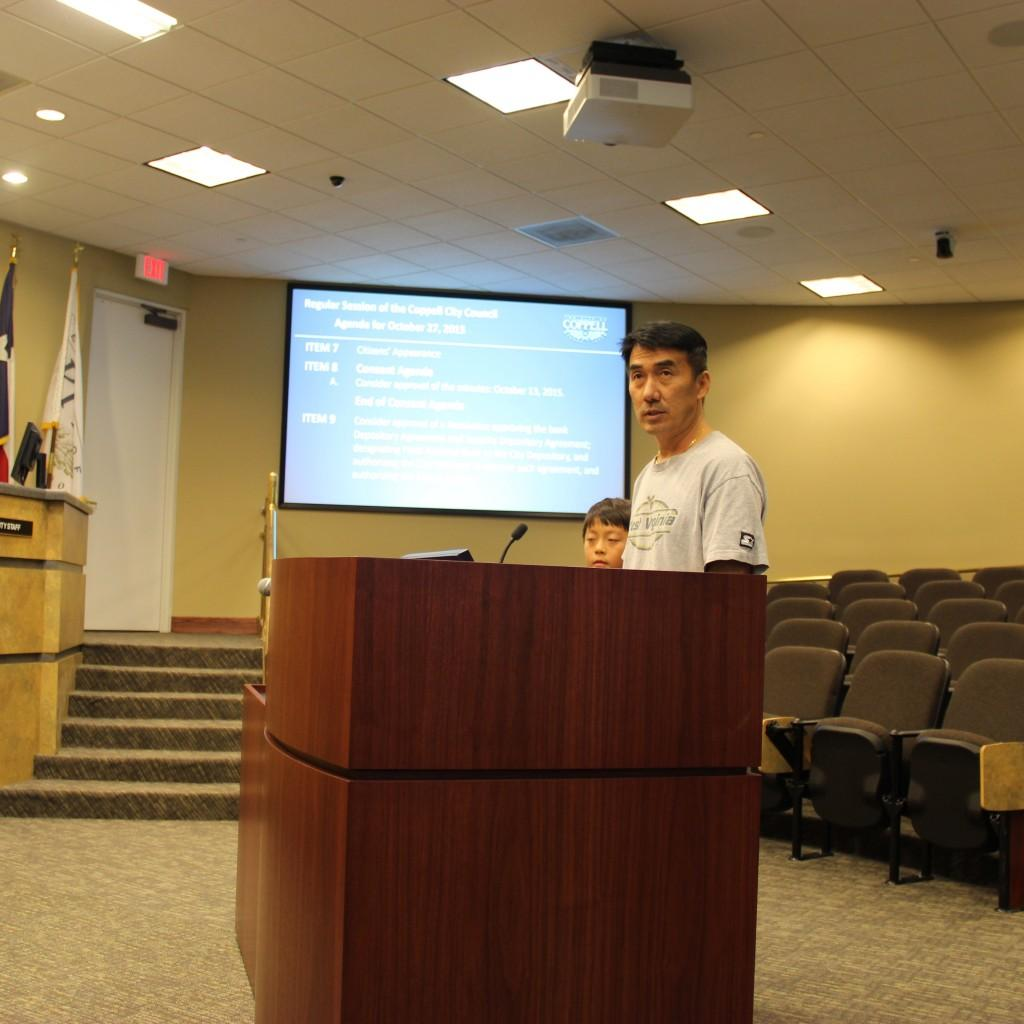 Coppell resident John Jun and his son Samuel Jun propose a need for long-term speed limit enforcements on Allen Road during the city council meeting on Tuesday at Coppell City Hall. John Jun is concerned about the safety of children walking home from school along the road. Photo by Jennifer Su.