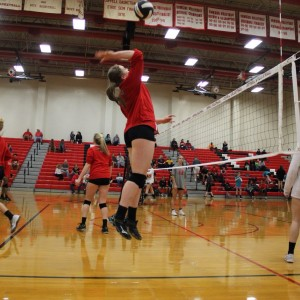 Coppell High School sophomore Breanne Chausse spikes the ball while warming up to defeat Trinity High School. The Cowgirls won all three sets, the first with a score of 25-9, 25-17, and 25-11 on Friday night's game in the CHS large gym. Photo by Megan Winkle.