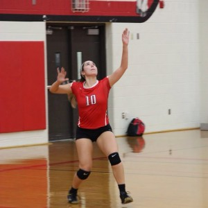 Coppell High School senior Caroline Riley serves the ball to begin the set against the Trojans. The Cowgirls won all three sets, the first with a score of 25-9, 25-17, and 25-11 on Friday night's game in the CHS large gym. Photo by Megan Winkle.