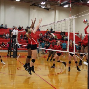 Coppell High School junior Katie Herklotz and freshman Mykayla Myers blocks the ball while the Trinity High School player spikes the ball. The Cowgirls won all three sets, the first with a score of 25-9, 25-17, and 25-11 on Friday night's game in the CHS large gym. Photo by Megan Winkle.