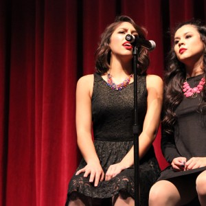 """For the third song of Thursday night's show, Coppell High School seniors and Respira Choir members Melissa Cannon and Allysa Garza perform Katy Perry's """"Dark Horse."""" The Coppell High School Respira Choir's Dessert Show was held in the CHS auditorium and had an intermission where guests could enjoy free desserts. Photo by Amanda Hair."""