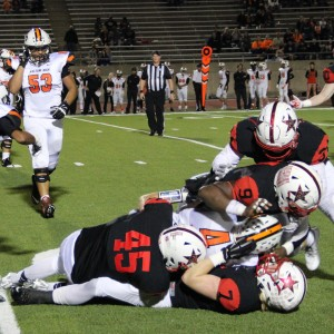 Coppell High School football players tackle the Haltom player with the ball during the third quarter. The Cowboys defeated the Buffalos Friday night at Buddy Echols Field 44-6. Photo by Megan Winkle