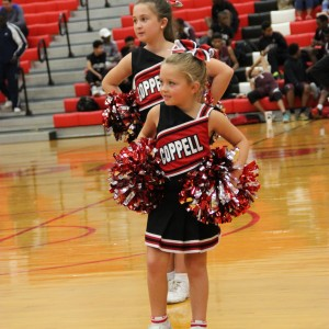 Coppell youth cheerleader performs a routine during halftime at the Varsity Basketball game against Mansfield Timberview. The cheerleaders helped the cowboys beat the Wolves Friday at home in the large gym 54-52.