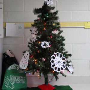Coppell High School Sidekick newspaper staff members put up the christmas tree in D115 on Monday during class. Students came together to make snowflakes and ornaments during the holiday season to decorate the tree.